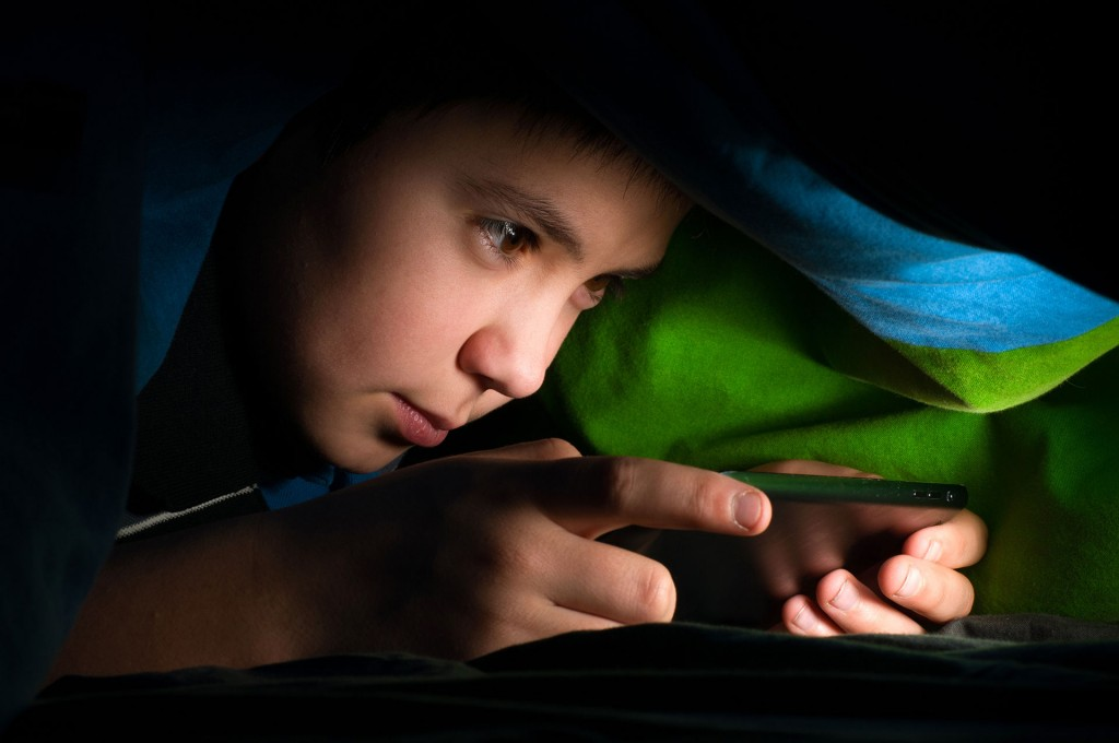 Boy on phone in bed
